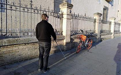 persona con bastón andando por acera con una bicicleta a un lado con riesgo para su seguridad