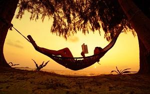 chica tumbada en hamaca en la playa sin hacer actividad física