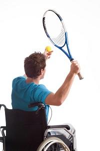persona en silla de ruedas con raqueta y pelota para practicar actividad física