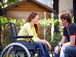 Una joven en silla de ruedas acompañada de un joven, un ejemplo de autonomía personal entre la gente joven