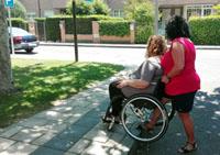 Una cuidadora atiende a una persona en silla de ruedas que lo necesita y que también puede aportar autonomía personal