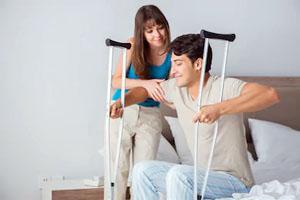 Una persona aprendiendo a levantarse de una silla para caminar con muletas