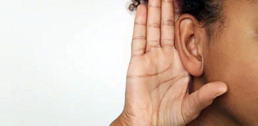 Un joven con discapacidad auditiva y con su mano en su oído escuchando algo