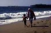 Una persona mayor con Parkinson y un niño caminando por la playa