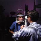 Médico oftalmólogo realizando una exploración a un niño para detectar algún Retinoblastoma