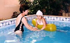 Niña con Síndrome de Rett realizando hidroterapia con su monitora