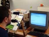 Usuario con su micrófono conectado al ordenador utilizando el programa de voz Dragon Speak como producto de apoyo