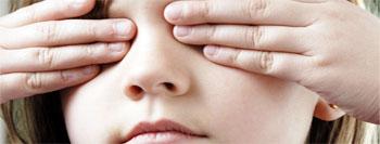 Una niña con los ojos tapados, representando la discapacidad visual