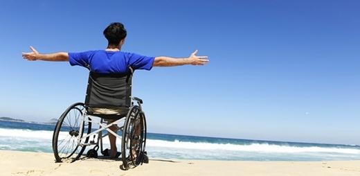 Fotografía de una persona en silla de ruedas frente al mar - Taller de autocuidado emocional para personas con ELA