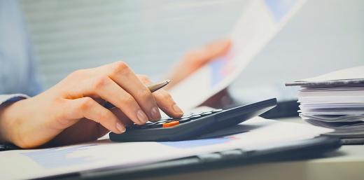 persona tecleando en un calculadora para averiguar importe de ayudas
