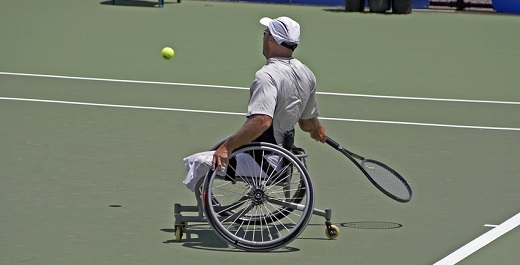 persona en silla de ruedas jugando al tenis y compartiendo beneficios del deporte