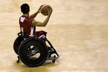 persona en silla de ruedas jugando al baloncesto y disfrutando beneficios del deporte