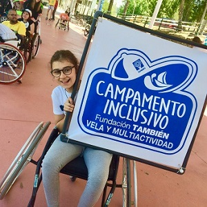 chica en silla de ruedas con el cartel de campamentos inclusivos