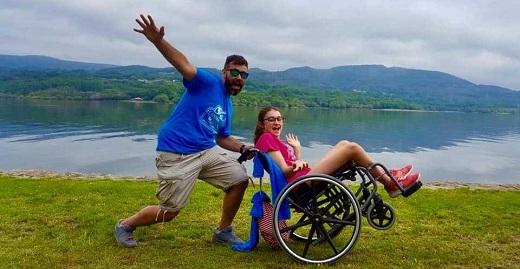 monitor sonriendo con chica en silla de ruedas frente al lago en los campamentos inclusivos