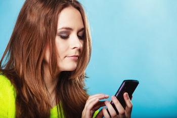 mujer buscando en móvil app para protegerse del cáncer de piel