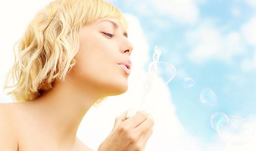mujer soplando pompas de jabón bajo el cielo azul y soleado, importante prevenir el cáncer de piel