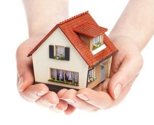 manos sosteniendo maqueta de una casa