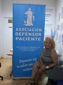 presidenta asociación defensor del paciente carmen flores delante de cartel de la asociación
