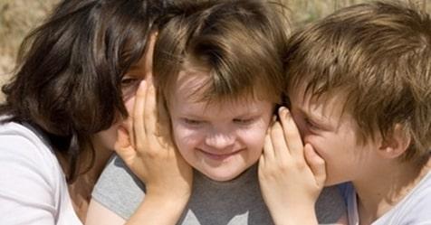 un niño y una señora susurran al oído a otro niño - derechos de la infancia con discapacidad