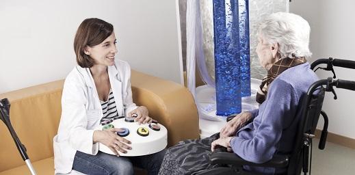 Enferemera con una persona en silla de ruedas con alzhéimer