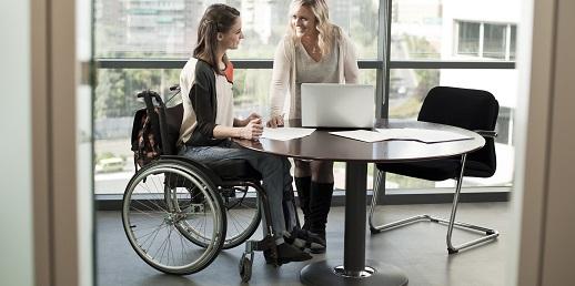 chica en silla de ruedas y su compañera, discapacidad en las empresas