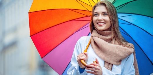 chica sonriendo bajo paraguas de colores, guía de las emociones