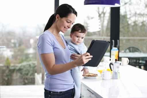 Una mamá joven con su hijo en brazos y mirando una tablet sonriendo como marca la guía de pensamiento positivo
