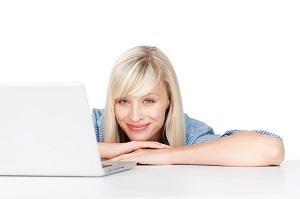 Una joven con cara de alegría y sentada al lado de un ordenador portatil ejemplo de la guía de pensamiento positivo