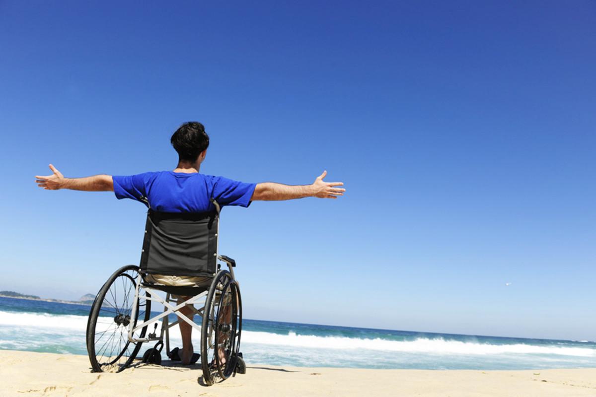 Un joven en silla de ruedas en la playa con las manos en alto en señal e alegría, ejemplo de la guía de pensamiento positivo