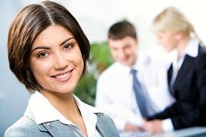 Una joven sonriendo en su puesto de trabajo ejemplo de la guía de pensamiento positivo