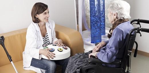 Hospitalización en casa persona mayor con auxiliar en el sofa de su salón