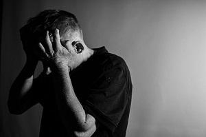Un hombre se tapa la cabeza con sus manos durante un ataque de ira