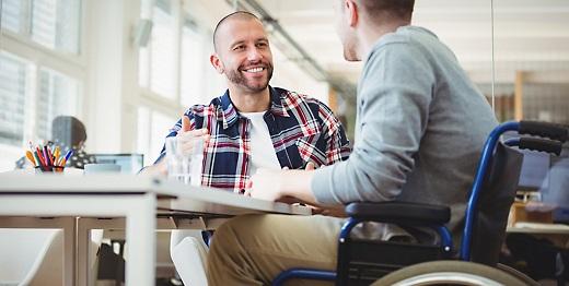 Dos jovenes en el trabajo, uno de ellos con lesión medular y en silla de ruedas