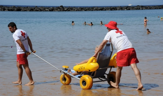 voluntarios de Cruz Roja ayudando a un bañista en un punto de baño del localizador de playas