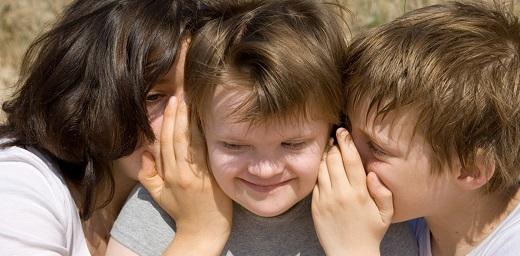menores con autismo, tres menores, dos hablando al oido del sentado en el medio