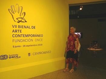 Merce Luz frente al cartel de la Bienal de Arte de Fundación ONCE, con la silla de apolo de fondo