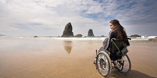 mujer y discapacidad chica en silla de ruedas en la playa