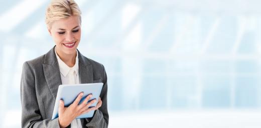 chica con traje sonriendo a ver en su tablet la oferta de trabajo