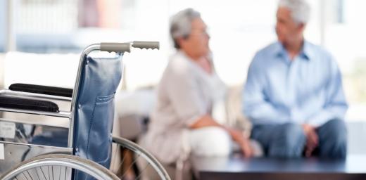 pareja de mayores de fondo y silla de ruedas en primer plano, personas con discapacidad