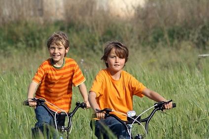 Recursos para una educación para todos, dos niños con bicicleta por el campo