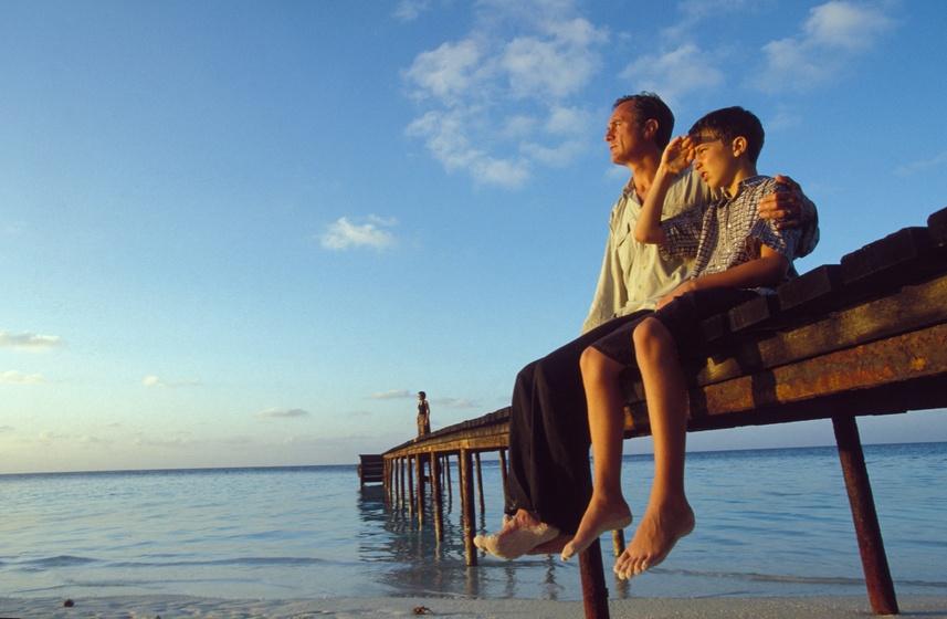 Un padre con un hijo sentados en una rampa en un lago