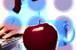 Una manzana y una raza junto a un ordenador donde una persona escribe un correo electrónico