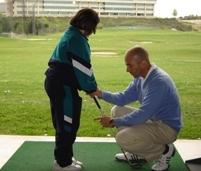 Deportes adaptados: Monitor con niña con discapacidad enseñándole golf