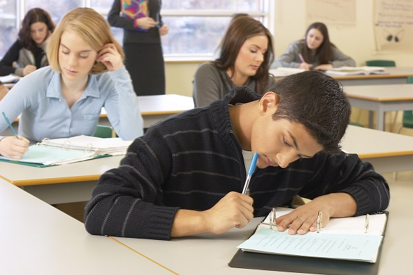 Estudiantes tomando apuntes en clase