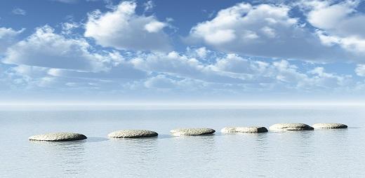 Paisaje de una paya con una piedras decorativas y encima de ella grandes nubes