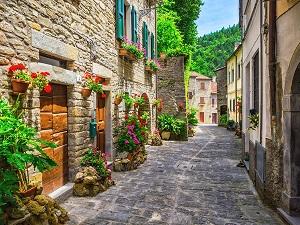 Calle de un pueblo con adornos de flores en sus casas, guía playas accesibles