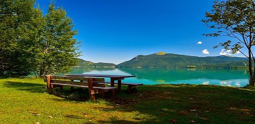 Guía playas accesibles, paisaje de un banco al lado de un lago con montañas