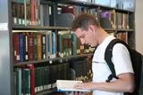 Estudiante en una biblioteca mirando la guía universitaria