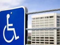 LIOUNDAU. SeñaL de discapacidad con una silueta de una persona en silla de ruedas conuna barrera metálica y de fondo un edificio de viviendas
