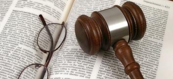 LIOUNDAU. Mazo de un juez y gafas encima de un libro de derechos